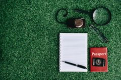 照相机、放大镜、护照指南针和空白的笔记本在绿草 免版税库存图片