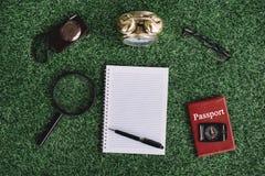 照相机、放大镜、时钟、指南针、护照和空白的笔记本在绿草 免版税库存照片
