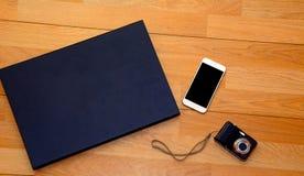 照相机、闭合的膝上型计算机和白色电话在木书桌上 免版税库存照片
