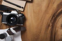 照相机和供应,在木桌上的空白的照片 免版税库存图片