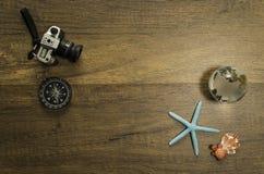 照相机和指南针在与海星世界玻璃大理石和乌龟的木桌上装饰 免版税库存照片