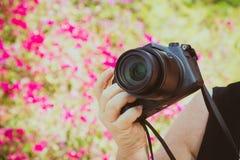 照相机在室外妇女摄影师的手上 免版税库存照片