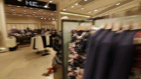 照相机在时尚有新的衣裳的商店机架附近移动 股票视频