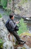 照相机在河岩石的人山 库存图片