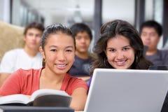 照相机女性微笑的学员到二 免版税库存图片