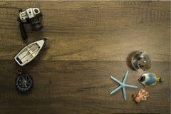 照相机小船和指南针在与海星世界玻璃大理石和乌龟的木桌上装饰 库存照片