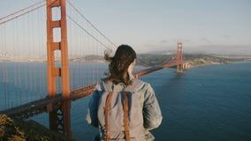 照相机接近有背包的,飞行头发年轻女性游人享受风景日落视图的在金门大桥美国 影视素材