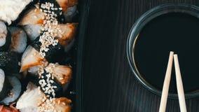 照相机提高 时髦地被放置的寿司在黑木背景设置了在酱油和中国竹棍子旁边 股票视频
