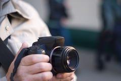 照相机数字式现有量他的拿着摄影师 免版税库存图片