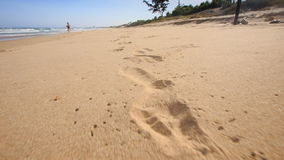照相机沿在湿沙子的脚印移动 股票录像