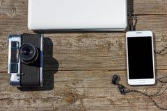 照相机电话和膝上型计算机在一张木桌上 免版税库存照片