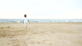 照相机的焦点在连续孩子后顺利地移动 一点愉快的男孩沙滩向海 儿童游戏 股票录像