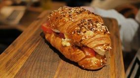 照相机的间距在新月形面包附近的充塞用蕃茄,红色鱼和软干酪,洒与芝麻和 股票视频