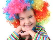 照相机看起来微笑的假发的小丑女孩 免版税库存图片