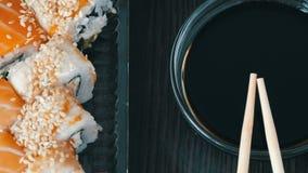 照相机移动  时髦地被放置的寿司在黑木背景设置了在酱油和中国竹棍子旁边 股票视频