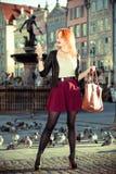 照相机老镇格但斯克的时兴的旅游女孩采取图片  免版税库存照片