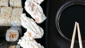 照相机调低 时髦地被放置的寿司在黑木背景设置了在酱油和中国竹棍子旁边 股票视频