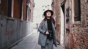 照相机跟随与照相机走沿美丽的街道的可爱的专业女性新闻工作者在威尼斯,意大利 股票视频