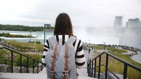 照相机跟随与背包走向拥挤观察台的旅游妇女在著名尼亚加拉大瀑布慢动作 影视素材