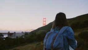 照相机跟随年轻旅游妇女与远足大小山的背包享受金门大桥史诗日落视图  股票录像
