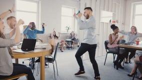 照相机跟随愉快的商人步行入办公室,做滑稽的庆祝舞蹈 不同种族的工作者笑和拍手4K 股票录像