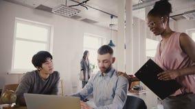 照相机跟随愉快的黑女性领导进入办公室,对同事的谈话 现代coworking的4K的不同种族的同事 股票视频