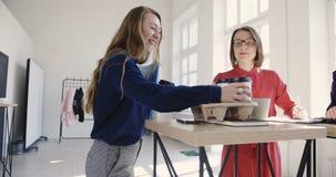 照相机跟随白肤金发的女性副经理运载的咖啡给见面在现代不同种族的轻的办公室的伙伴 股票录像