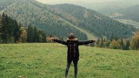 照相机跟随走在山的徒步旅行者环境美化与培养胳膊入空气的少女 影视素材