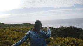 照相机跟随跑在往史诗岩石大瑟尔海洋海岸线的黄色花观点中的年轻愉快的妇女 股票录像