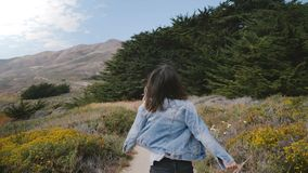 照相机跟随跑沿往大岩石的一条小道路和森林的年轻愉快的妇女在大瑟尔海岸线加利福尼亚 股票录像