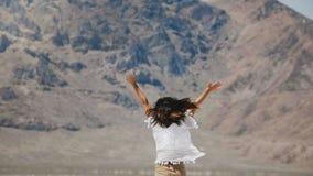 照相机跟随转动年轻愉快的自由的妇女跳跃和与开放的胳膊和微笑在盐沙漠湖的飞行的头发 股票录像