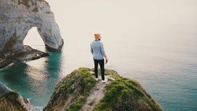 照相机转动年轻愉快的白种人人身分在史诗日落海景在诺曼底岩石岸峭壁顶部 股票录像