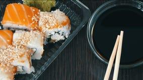 照相机迅速移动 时髦地被放置的寿司在黑木背景设置了在酱油和中国竹棍子旁边 多种 股票视频