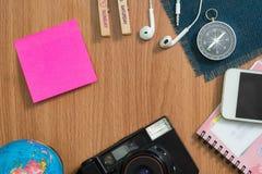 照相机,地球,耳机,指南针,电话,笔记本,关于木书桌的稠粘的笔记 免版税图库摄影