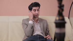 照相机从右到左移动并且采取一个年轻商人谈话在电话 股票视频