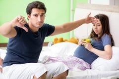 照看他怀孕的妻子的年轻丈夫 免版税图库摄影