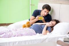 照看他怀孕的妻子的年轻丈夫 库存图片