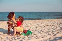 照顾与她的婴孩的戏剧海滩的 免版税库存图片