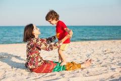 照顾与她的婴孩的戏剧海滩的 库存照片