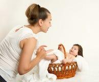 照顾与婴孩的谈话在白色毛巾的篮子的,家庭观念,被定调子的黄色 免版税库存照片