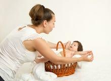 照顾与婴孩的谈话在白色毛巾的篮子的,家庭观念,被定调子的黄色 免版税图库摄影