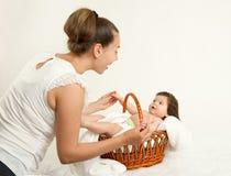 照顾与婴孩的谈话在白色毛巾的篮子的,家庭观念,被定调子的黄色 库存照片