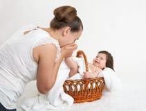 照顾与婴孩的谈话在白色毛巾的篮子的,家庭观念 库存照片