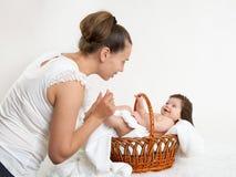 照顾与婴孩的谈话在白色毛巾的篮子的,家庭观念 免版税图库摄影