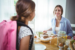 照顾互动与她的女儿,当食用早餐时 免版税库存图片