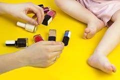 照顾使用与她的女儿化妆用品,指甲油,特写镜头 免版税库存照片