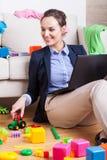 照顾使用与她的孩子和检查电子邮件 库存图片