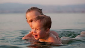 照顾使用与她的海滩的年轻儿子 股票视频