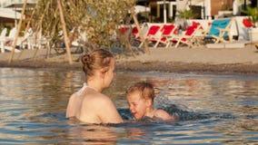 照顾使用与她的海滩的年轻儿子 影视素材