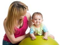 照顾做体操给健身球的婴孩 库存图片